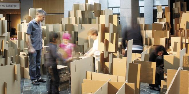 Agglomération du collectif 1x1x1. Initiation aux notions de construction par l'utilisation d'un seul matériau, des panneaux de carton ondulé double, modulés en trois tailles. Divisés en plus de 1800 morceaux, la multiplication et l'empilage des éléments créent une présence massive et complexe tout en restant transparents et aériens. L'installation rappelle ainsi la porosité et la richesse des villes qui se développent de façon quasi organique à partir d'éléments somme toute répétitifs et artificiels. Photo Olivier Vallerand